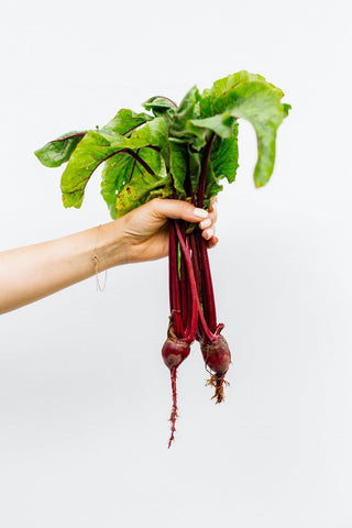 A hand holding 2 beetroots