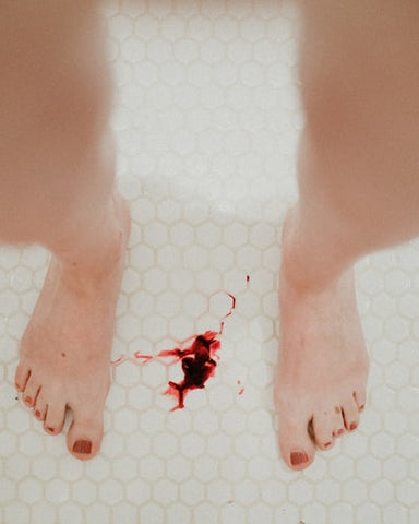 A woman standing in the bathroom with blood on the tile