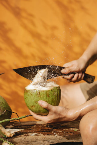 A hand with a knife cutting open a tender coconut
