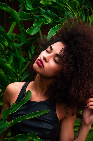 A woman with curly hair posing behind a green leafy background