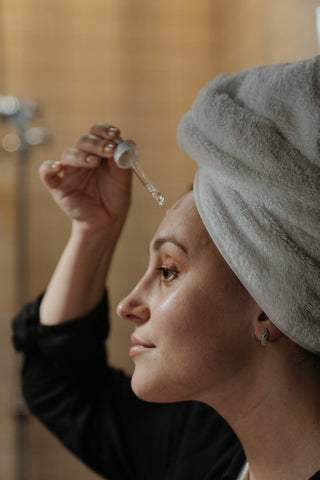 A woman in front of a mirror with a towel on her hair applying an oil on her skin