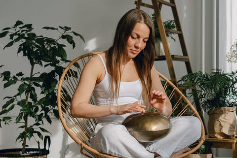 A woman sitting on a chair playing an instrument