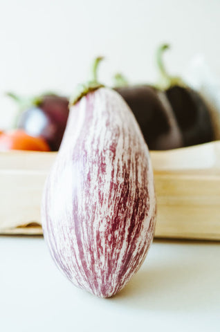 A purple Eggplant resting on a plate