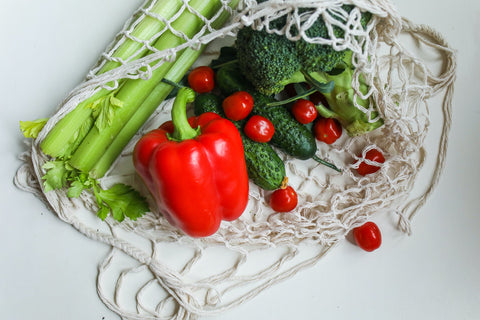 A white netted bag with leeks, bell pepper and some cherry tomatoes