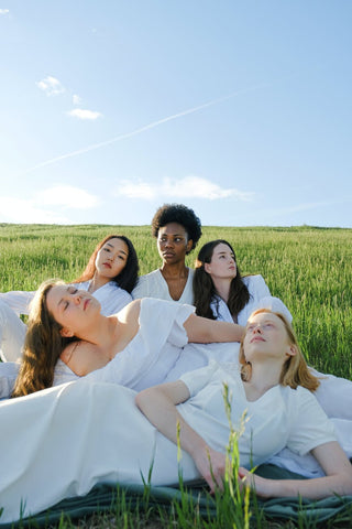 A group of varied women in white dresses sitting on the ground