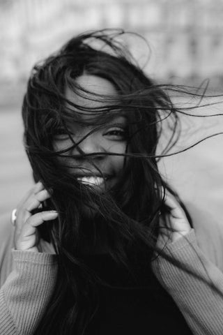A smiling woman with her hair all over her face