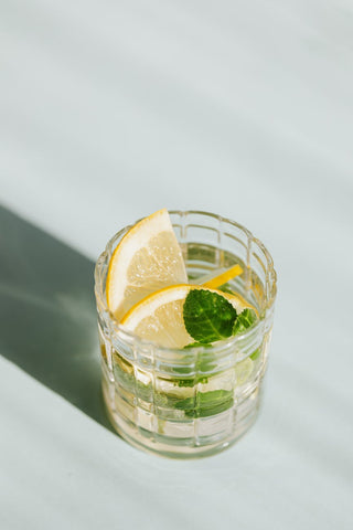 A glass of infused water with two slices of lime and a sprig of mint leaf
