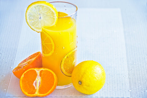 A glass of orange juice with slices of orange near the glass