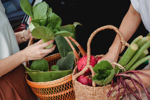 Two woman holding baskets with variety of vegetables