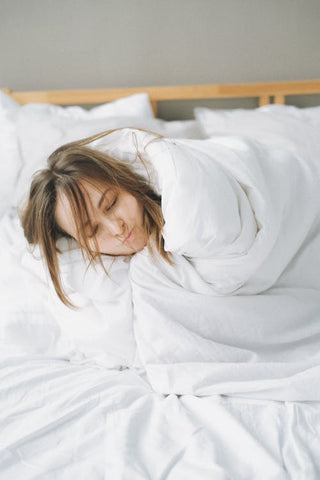 Woman sleeping in her bed with messy hair