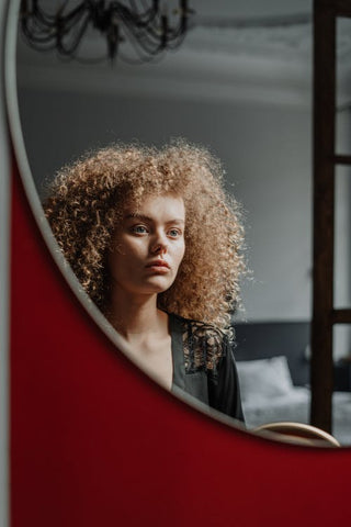 Woman with curly hair looking at herself in the mirror