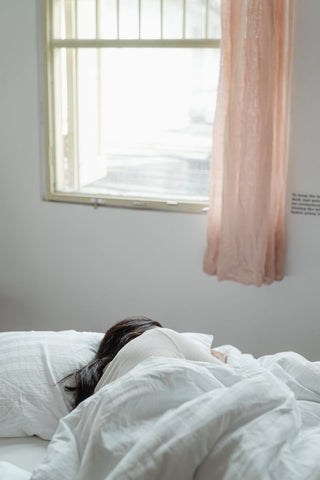 Woman sleeping under a white blanket