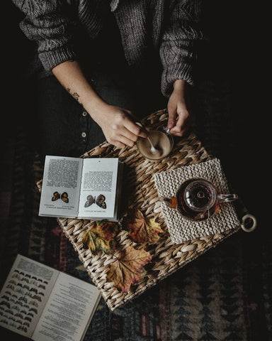 Woman making tea with books beside her
