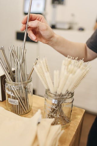 Hand picking out a stainless steel straw