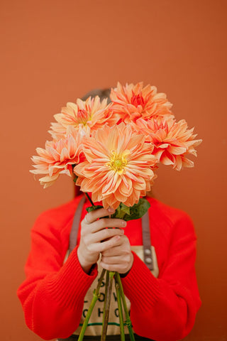Woman holding a bunch of orange flowers covering her face