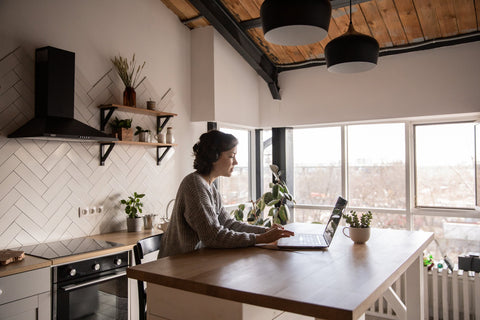 Girl working on a laptop in a room with natural light