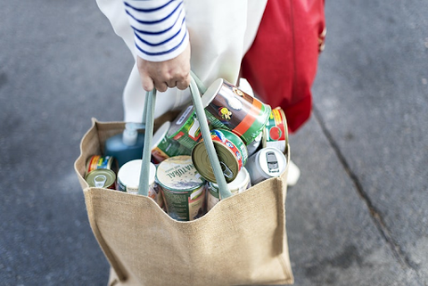 Hand holding a bag full of grocery items