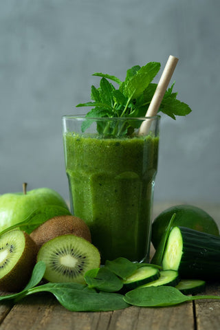 A glass of green smoothie with few pieces of Kiwi and spinach leaves around it