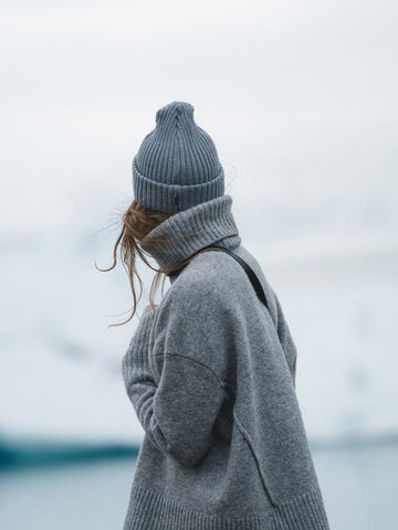 Woman in fully winter clothes looking at glaciers
