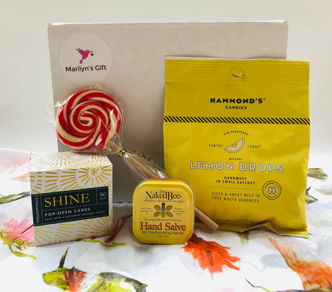 Marilyn's Gift Soothing Box is filled with items to help you feel better.  The box includes: an inspirational box of messages, hand salve, a peppermint lollipop and lemon drops.  You get to choose the fifth item.  Options to choose from are 1) a mask with 2 layers of material, 2) Basic Jane Relax spray, 3) Basic Jane Awake Spray or 4) CBD rollon.