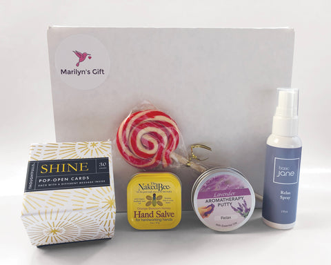 This gift box is sure to calm your mood.  Included are items to relax you: some Basic Jane lavender pain relief spray, lavender putty, Naked Bee hand salve, a peppermint lollipop and Compendium motivational cards.