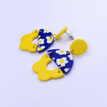 Load image into Gallery viewer, Polymer clay statement earrings with daisy motif and flower pattern in vibrant yellow and royal blue color.