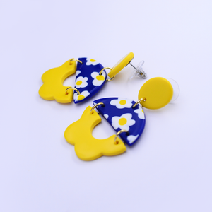 Polymer clay statement earrings with daisy motif and flower pattern in vibrant yellow and royal blue color.
