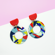 Load image into Gallery viewer, Polymer clay big statement hoop drop earrings with dynamic graphic pop art hoop and red studs. Vibrant, colorful, playful, modern and chunky earrings.
