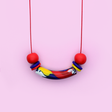 Load image into Gallery viewer, Polymer clay adjustable lenght two way to wear front or back necklace with pop art graphic beads. Primary colors red blue yellow beads and red waxed cotton cord. Funky, cool and playful.