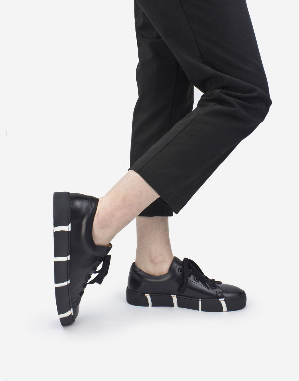 Black leather minimal classic low top sneaker with recycled striped sole by designer Georgina Goodman