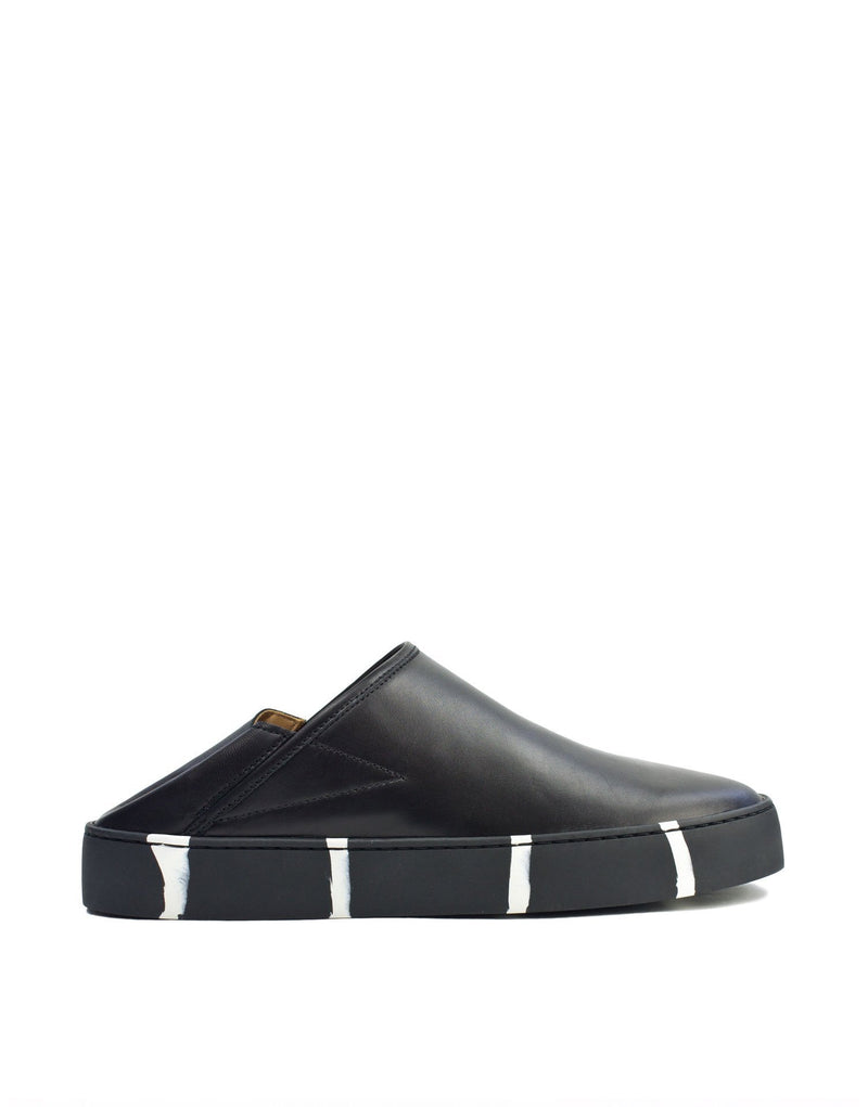 Black leather minimal classic slip on sneaker with recycled striped sole by designer Georgina Goodman