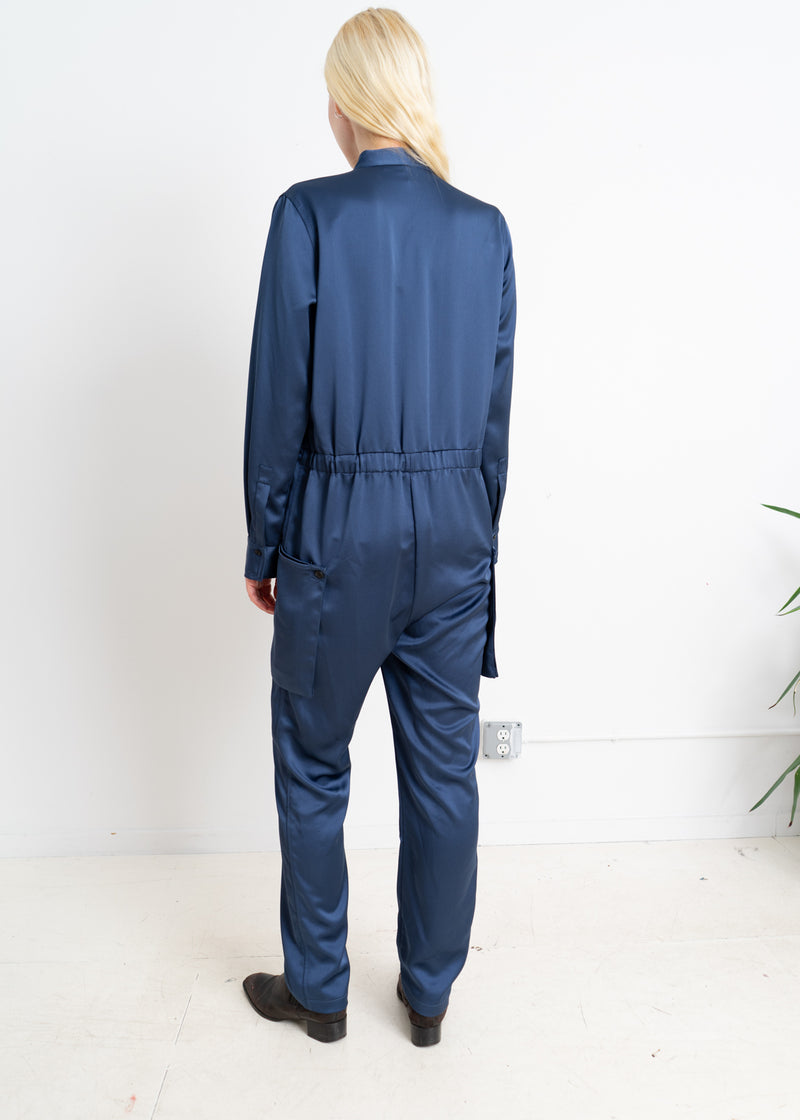 Blue viscose long sleeve jumpsuit with exterior pockets.