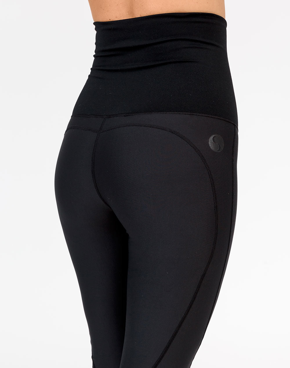 back view of a pregnant woman wearing black 3/4 maternity leggings