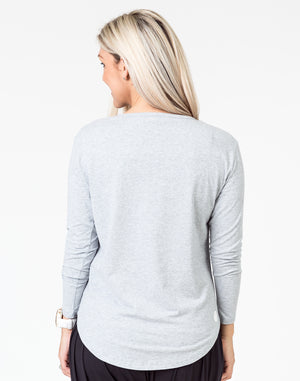 back view of a mom wearing a gray maternity top with long sleeves