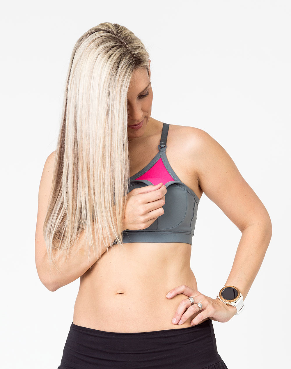 mom wearing a gray racerback nursing bra with one dropdown cup unclipped and pink lining