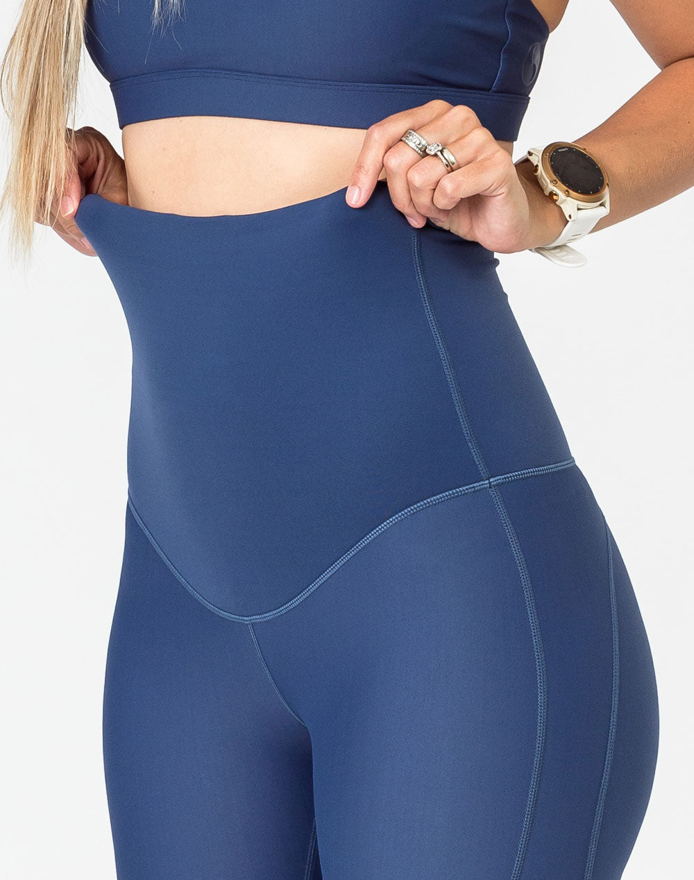 close up view of blue maternity leggings with an attached belly band that goes over the bump