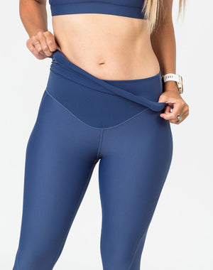 happy mom wearing blue maternity leggings with the over the bump compression panel folded over