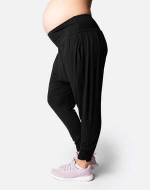front view of a mom wearing black maternity harem pants with the pants legs pulled up