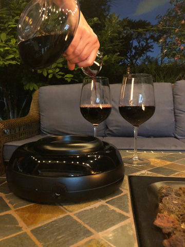 Aerisi wine aerating unit on patio table near fire pit with blue outdoor couch in background, hand holding decanter and pouring red wine into 2 wine glasses