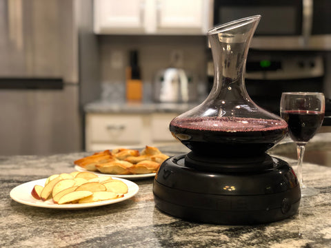 Aerisi Wine Aerator with red wine in decanter and a glass of red wine standing to the right of the Aerisi unit sitting on a white and black granite kitchen counter next to a plate of sliced apples.top