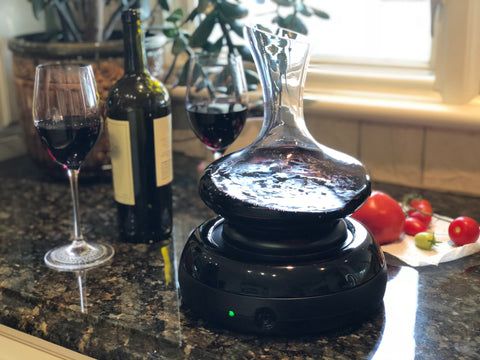 Aerisi wine aerator with decanter with red wine sitting on dark granite counter top near a kitchen window with 2 glasses of red wine and a wine bottle and green plant behind it