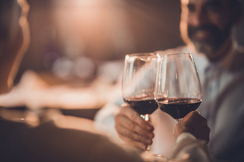 Gentleman in a white dress shirt and beard sitting at a restaurant table facing us, his companion sitting across from him with their back toward us, toasting each other each holding a glass of red wine, soft warm light in the background