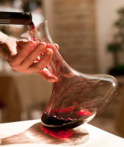 Hand tilting wine decanter on wooden table pouring a bottle of red wine flowing along sides of glass decanter to aerate