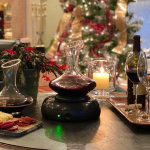 Aerisi Wine Aerator and glass decanter filled with red wine sitting on coffee table with Christmas cactus plant and cream colored lit candle in a glass holder. Christmas tree with soft white twinkly lights decorated with gold and red ribbon in background.