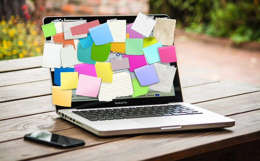 macbook with a screen covered in post its