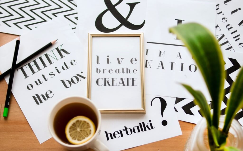 blog post writer's desk of random notes that say 'think outside the box' and 'think breathe create'