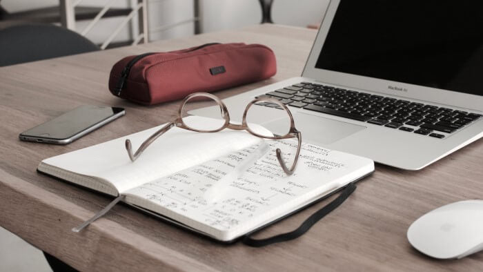 Eyeglass on top of the open notebook