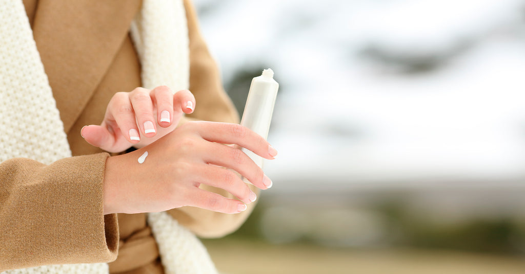 Woman outside in winter clothes putting lotion on her hands