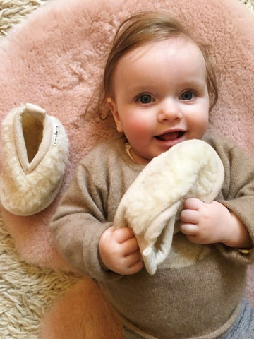 baby pictured lying on top of a binibamba sheepskin pram liner holding her merino baby booties