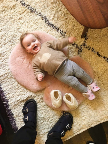 Baby lying onto of Binibamba sheepskin snuggles, a natural, hypoallergenic playmat in Rose pink that  also doubles up as a buggy liner in rose pink.